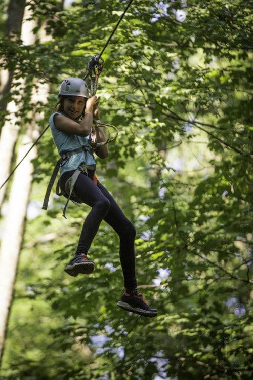 jeune fille sur tyrolienne dans parcours accrobranche